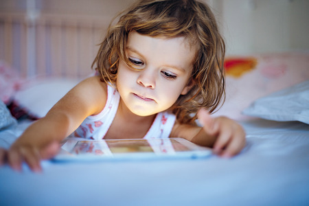 little girl playing tablet at home on a bed