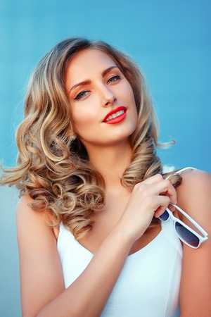 Portrait of a beautiful blond girl with long wavy hair smiling wearing white dress handing a white sunglasses Stock Photo