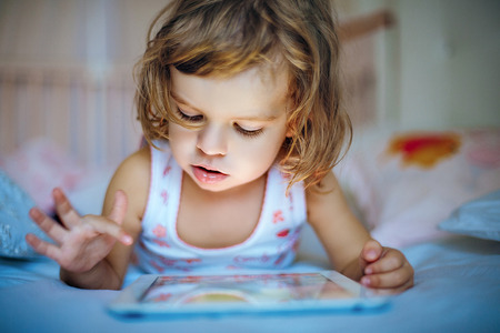 hands holding house: little girl playing tablet at home on a bed