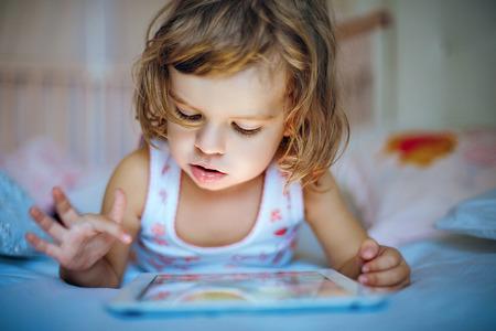 familias felices: niña jugando tablilla en el país en una cama Foto de archivo