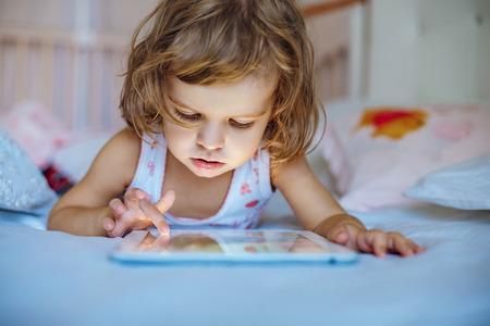 computadora caricatura: niña jugando tablilla en el país en una cama Foto de archivo