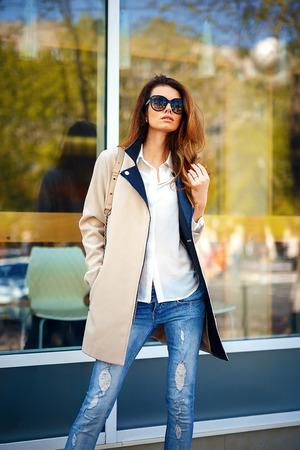 girl in a beige coat near the shop