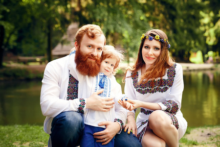 a young baby: Happy ukrainian family with little son in traditional ukrainian dress in a countryside, park