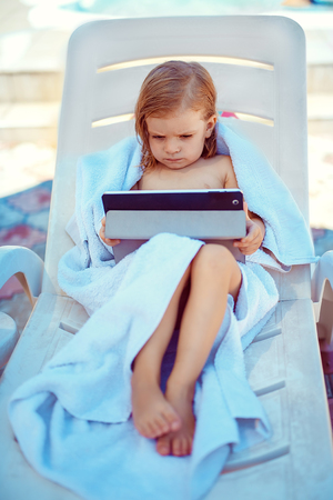 girl using laptop: Small girl of a 3 years old lying on a white towel on a lounger playing  tablet