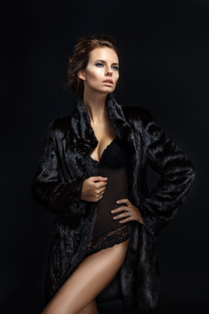 woman nude sexy: Fashion seductive brown hair lady in an elegant fur coat and black underwear on a dark background