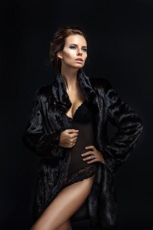 jeune femme nue: Mode séduisante dame cheveux bruns dans un manteau de fourrure élégante et sous-vêtements noirs sur un fond sombre