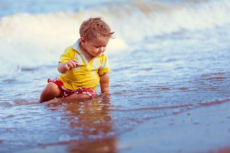 red shorts: Boy in yellow shirt, red shorts, sit on the beach close to the water, play