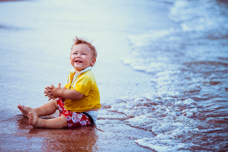red shorts: Boy in yellow shirt, red shorts, sitting on the beach close to the water, playing, laughing