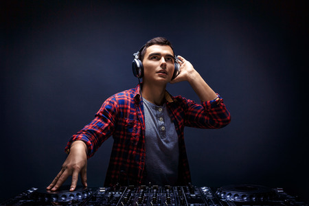 Closeup portrait of confident young DJ with stylish haircut and headphones on head mixing music on mixer looking up while standing isolated on dark background