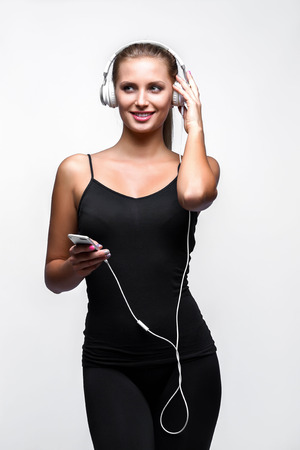 stay on course: Beautiful fit caucasian lady with headphones listening music. Isolated on gray background. Stock Photo