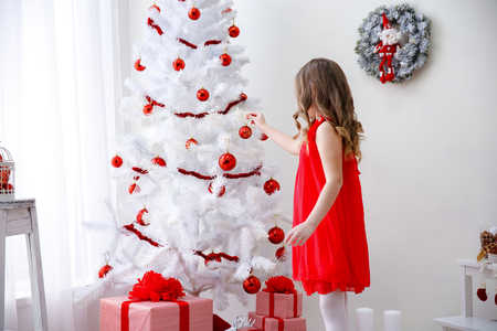 decorating christmas tree: Adorable little toddler girl with curly hair  decorating a beautiful Christmas tree Stock Photo