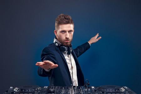 dj mixer: Man in dark  suit play music on a djs mixer. Studio shot.