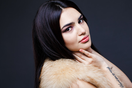 seductress: Fashion seductive dark hair lady in an elegant fur coat on a dark background Stock Photo