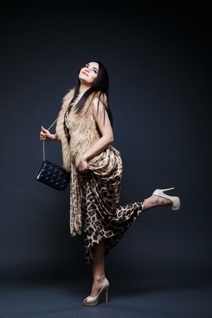 seductress: Fashion seductive black hair lady in an elegant fur coat and leopard dress on a dark background