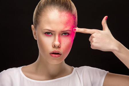 frash: Concept of a portrait of young blond girl with a lot of pain of suicide on her face, pink make-up, purple eyeshadows looking at you with hand pistol on black background. Social theme. Stock Photo