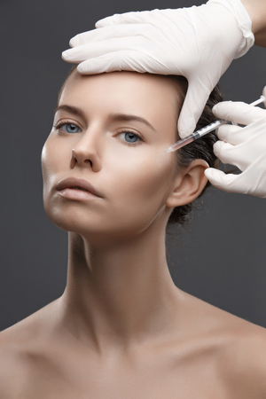 injection woman: Portrait of young woman getting cosmetic injection. Clean Beauty.  Opened eyes. Stock Photo
