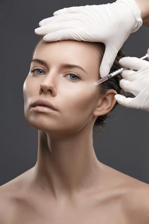 inyeccion: Retrato de una mujer joven que consigue la inyección cosmética. Belleza limpio. ojos abiertos. Foto de archivo