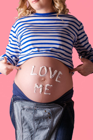bellybutton: Pregnant woman writing love me word on her belly. Trendy Pink background.