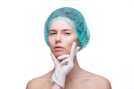 surgeons hat: Medical examination face of beautiful woman by hands in glove - close-up portrait isolated on white Stock Photo