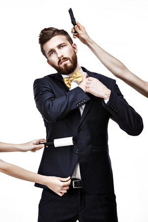 Bearded man in dark suit. sticky brush for cleaning clothes from dust. Stock Photo