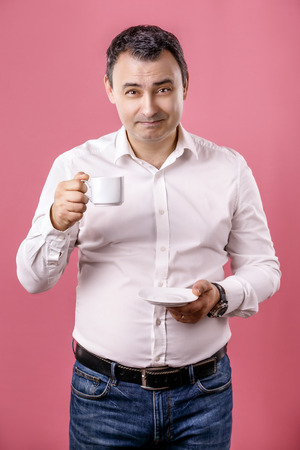 simultaneous: Portrait happy, smiling business man, lawyer drinking cup coffee isolated pink background.
