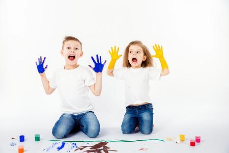 nene y nena: Dos bastante amigos de niño chico y chica con camisa blanca y pantalones vaqueros azules, estilo de pelo de moda, descalzo, dibujando en una hoja blanca de papel por las pinturas aisladas en blanco. estudio de disparo. Mostrando las manos en pintura