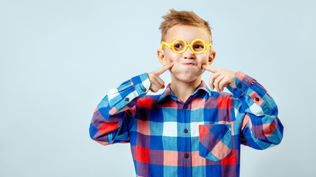 ideological: Little boy wearing colorful plaid shirt, plastic glasses having fun in the studio