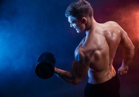 athletic body: Closeup of a handsome power athletic man bodybuilder doing exercises with dumbbell. Fitness muscular body on dark  smoke background. Perfect male. Awesome bodybuilder, tattoo, posing.