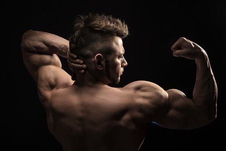 Strong Athletic Man Fitness Model posing back muscles, triceps, latissimus over black background 스톡 콘텐츠