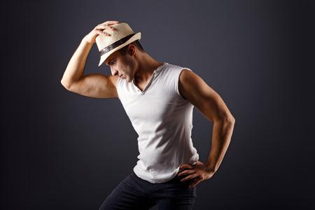 fedora: Man fashion model, stylish young man wearing fedora hat standing posing, over black background
