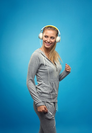 stay on course: Beautiful blond fit caucasian lady in grey sport  with headphones listening music. Isolated on blue background.