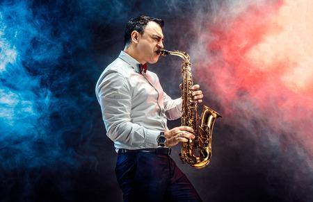 Elegant saxophonist plays jazz on dark background in a smoke Archivio Fotografico