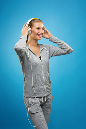 vertical wellness: Portrait of young blonde woman in sportswear listening to music with cell phone.Studio shot. Blue background. Isolated. Stock Photo