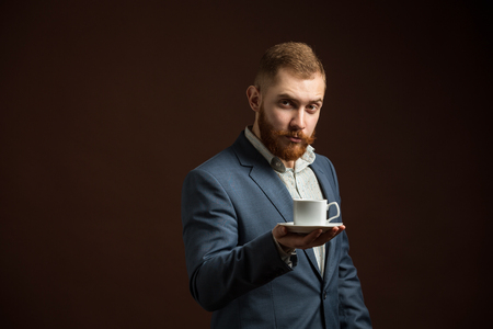 aristocracy: Portrait of red haired elegant man in suit with cup of coffee looking at camera.Isolated. Stock Photo