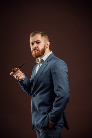 aristocracy: Portrait of handsome confident man in suit holding smoking pipe against of brown background.Isolated.