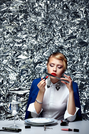 lip stick: Portrait of young blonde woman doing make-up at table with red lip stick looking at knife reflection