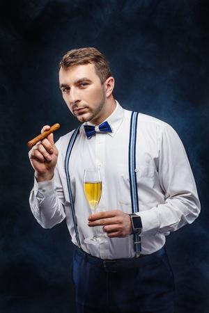 Portrait d'un bel homme en n?ud papillon et bretelles tenant le verre de boisson et cigare tout en regardant la caméra. Fumée sur fond. studio shot
