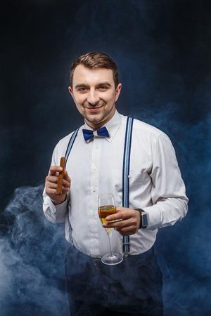 Portrait d'un homme souriant beau dans n?ud papillon et bretelles tenant le verre de boisson et cigare tout en regardant la caméra. Fumée sur fond. studio shot