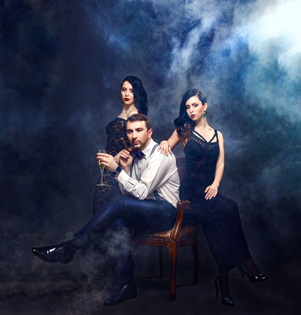 Portrait of handsome man with drink and cigar sitting on chair surrounded by two beautiful black-haired women in dresses.Smoky background.Studio shot