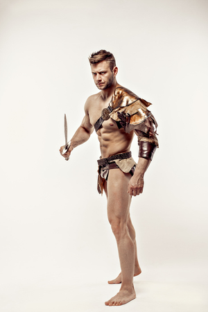 gladius: Portrait of handsome strong gladiator in leather costume holding sword and looking away.Studio shot,isolated. Stock Photo