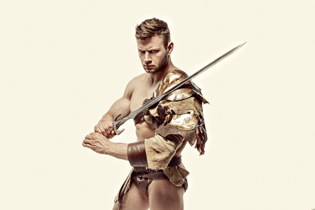 bagged: Portrait of muscular and strong gladiator in leather bagged clothes holding sword. Isolated.