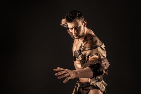 gladius: Portrait of handsome muscular gladiator with sword near face. Isolated. Studio shot. Black background Stock Photo