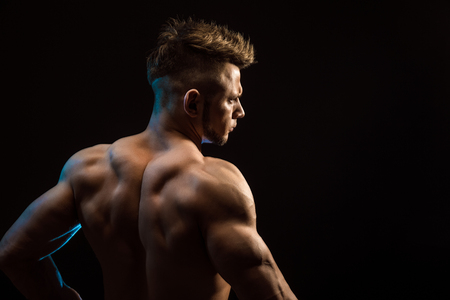 latissimus: Strong Athletic Fitness Man posing back muscles, triceps, latissimus over black background Stock Photo