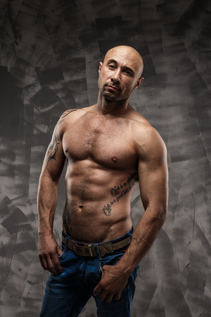 tough guy: Shirtless muscled fitness man. Cool looking. Tough guy. Brown eyes. Bald. Tanned skin. Studio shot on grey abstract background.