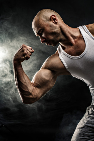 tank top: male in white tank top with strong muscles on the black background