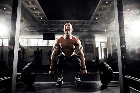 デッドリフトのジムで運動をしている上半身裸の若い男。モチベーションのために叫んでください。 写真素材 - 57159557