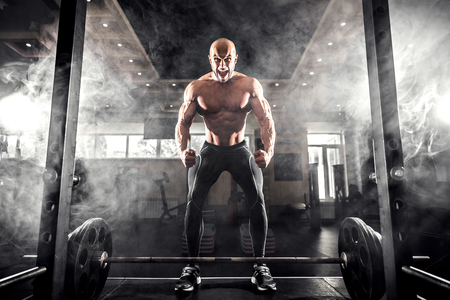 snatch: Athlete motivates screaming before barbells exercise at gym. Smoke Stock Photo