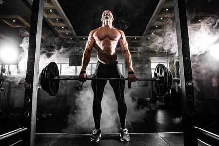 Młoda półnagi mężczyzna robi martwy ćwiczenia na siłowni. Krzyczy motywacji