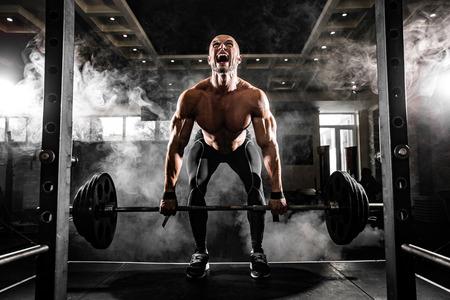 デッドリフトのジムで運動をしている上半身裸の若い男。モチベーションのために叫んでください。 写真素材 - 57159561