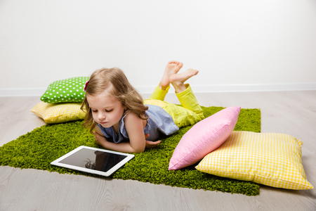 attentiveness: The little girl in a striped t-shirt, yellow jeans with a flowing hair, lies on a green rug with multi-colored pillows looks in the tablet